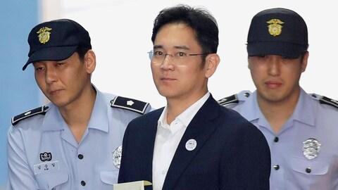 Le vice-président et héritier de Samsung, Jay Y. Lee, vêtu d'un complet, arrive en cour entouré de deux agents en uniforme.