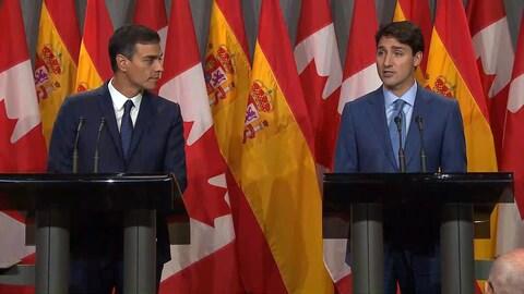 Un homme debout derrière un lutrin regarde et écoute un autre, à sa gauche, qui répond aux questions de journalistes devant plusieurs drapeaux canadiens et espagnols.