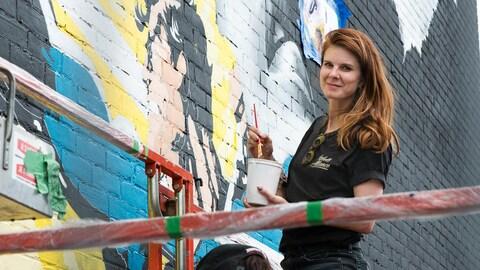 Sandra Chevrie prend la pose alors qu'elle peint une mural au Festival Mural, en juin 2018