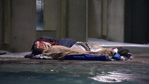 Une personne itinérante dormant dans la rue, dans des couvertures, en hiver.