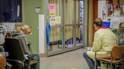 Une infirmière et une bénévole de Services de santé Alberta sont assises dans un couloir d'hôpital.