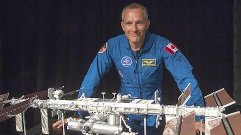 L'astronaute canadien David Saint-Jacques devant une maquette de la Station spatiale internationale.