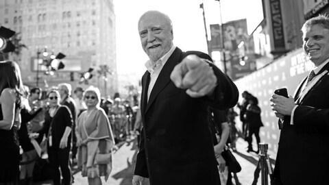 Photographie en noir et blanc de Scott Wilson qui pointe du doigt vers l'appareil photo.