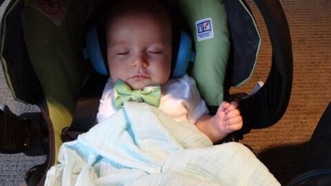Un bambin dort dans un siège pour bébé