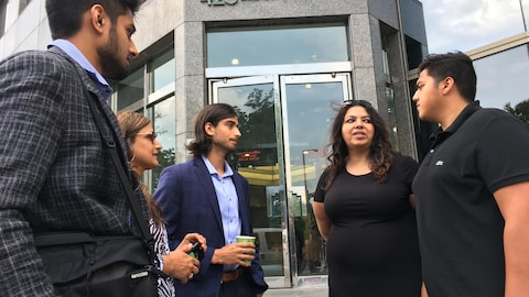 Un groupe de cinq personnes se parlant devant une porte.