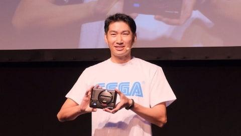 Un représentant de la compagnie Sega tient dans ses mains une petite console, la Sega Genesis Mini.