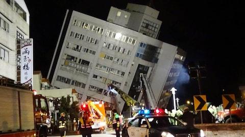 Des secouristes  près d'un immeuble incliné sur le côté à Hualien après un séisme.