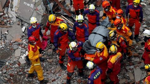 Vue en plongée de secouristes qui s'affairent autour d'un corps recouvert d'une housse.