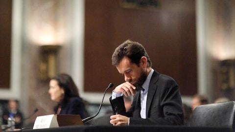 Mme Sandberg est hors-champ. M. Dorsey a l'air pensif alors qu'il prend des notes. Les deux sont assis à la table des témoins.