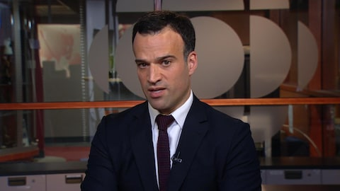 Un homme à la chevelure noire, en veston-cravate, regarde droit vers la caméra.