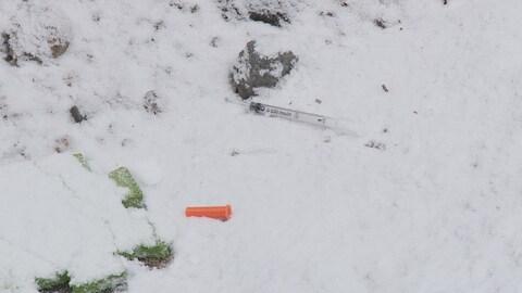 Une seringue souillée dans la neige.