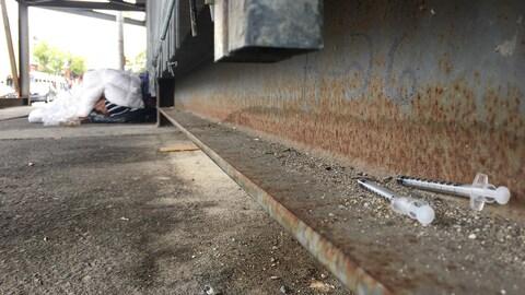 Des seringues souillées, sur le sol, près d'un sans-abri qui dort.