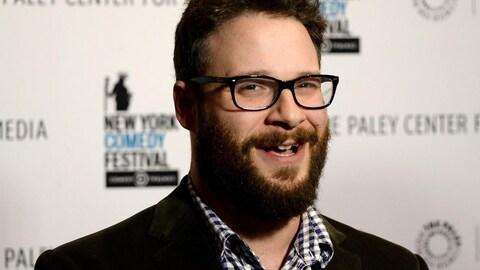 Seth Rogen sourit pour la caméra devant une affiche du New York Comedy Festival.