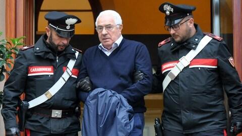 Deux policiers escortent un homme menotté.