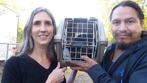 Une femme et un homme aux cheveux longs tiennent entre eux à hauteur de visage une boîte de transport de chat avec un chat à l'intérieur. Les deux humains sourient, le chat a l'air mécontent.