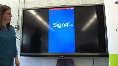 Une femme se tient près d'un écran accroché au mur, sur lequel on voit la page d'accueil de l'application Sign4l.