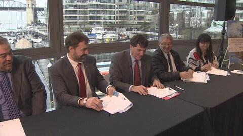 Le ministre Dominic LeBlanc (milieu) signe le protocole d'entente de gouvernance concertée pour protéger la côte nord du Pacifique.