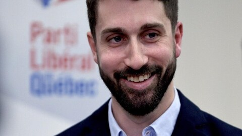 Un homme souriant, devant la pancarte du Parti Libéral du Québec.
