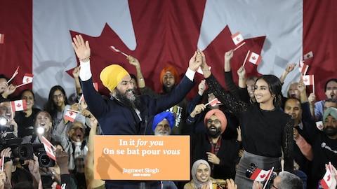 Jagmeet Singh en compagnie de sa conjointe et de militants du NPD qui agite des drapeaux du Canada sur une scène.