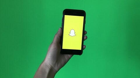 Un téléphone mobile avec le logo de Snapchat tenu dans une main devant un tableau vert