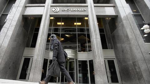 Un piéton passe devant la façade du siège social de SNC-Lavalin, à Montréal.