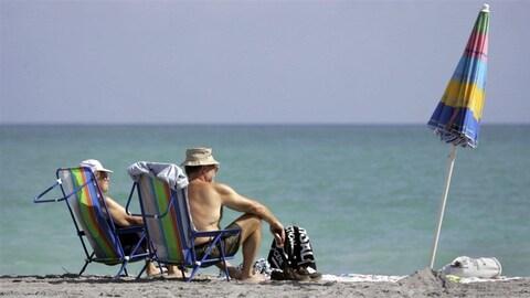 Un homme et une femme assis sur des chaises à la plage.