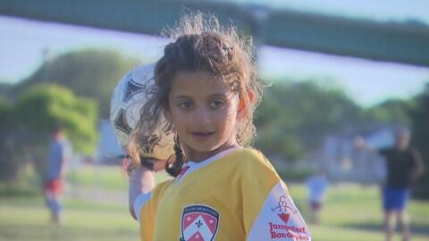 La jeune fille tient un ballon dans sa main droite