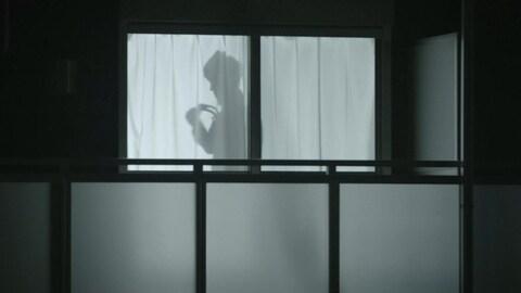 Ombre d'un homme faisant un nœud de cravate, la nuit, derrière un rideau