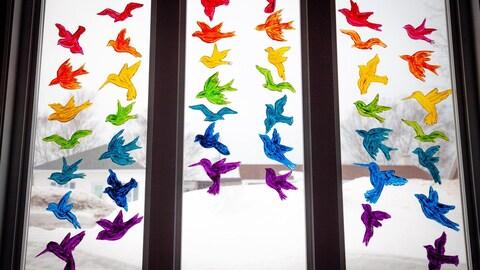 Une fenêtre avec des oiseaux peints aux couleurs de l'arc-enciel