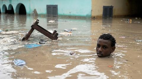 Un garçon nage dans l'eau qui inonde une rue de Mogadiscio.