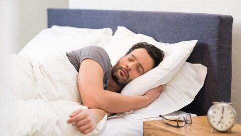 Un homme dort seul dans un lit.