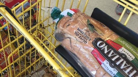 Une souris dans un sac de pain dans un panier d'épicerie.
