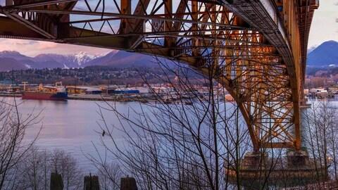 Une photographie des dessous d'un pont métallique avec en arrière-plan la rive nord de Vancouver avec des monts enneigés.