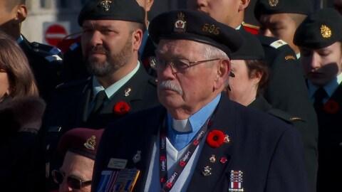 Un vétéran portant plusieurs médailles militaires est debout à l'extérieur lors d'une cérémonie du jour du Souvenir.