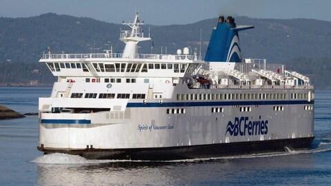 Le traversier Spirit of Vancouver Island, un gros bateau blanc et bleu, est dans l'eau.