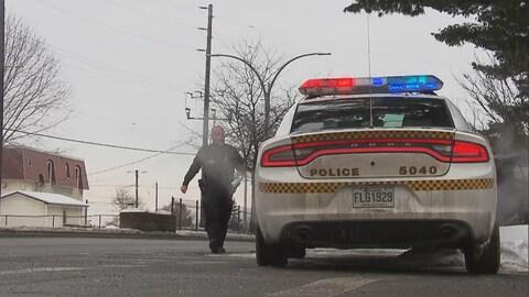Un agent qui se dirige vers son véhicule dans la rue, l'hiver