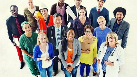 Groupe de personnes debout avec des costumes, uniformes ou objets reliés à différents métiers.