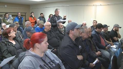 Des dizaines de personnes rassemblées dans une salle commune. Plusieurs sont assis alors que d'autres sont debout, à l'arrière du groupe.