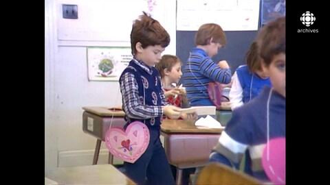 Garçon, sac en coeur en bandoulière, consultant le prochain valentin qui a à distribuer dans une classe d'élèves du primaire