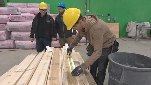 Un jeune stagiaire mesure une planche de bois.