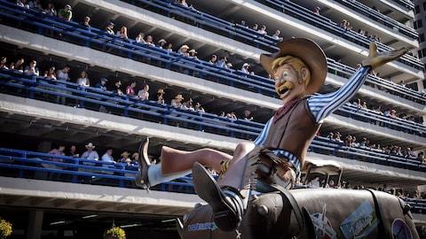 Les spectateurs regardent une représentation de cowboy qui fait du rodéo passer.