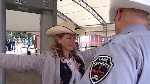 Un agent de sécurité scanne une femme avec un chapeau de cowboy à l'aide d'un détecteur de métal portatif. Derrière eux se trouve un portique de détection situé sous la tente à l'entrée du Stampede de Calgary.
