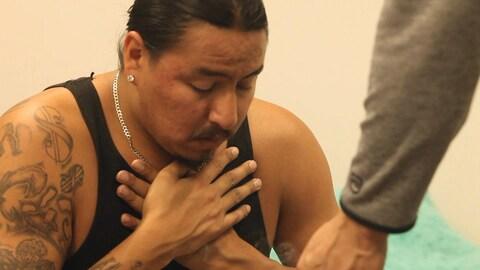 Plan serré d'un homme qui prend part à une cérémonie de purification autochtone.