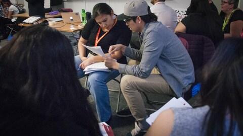 Deux jeunes regardent des notes dans un cahier.