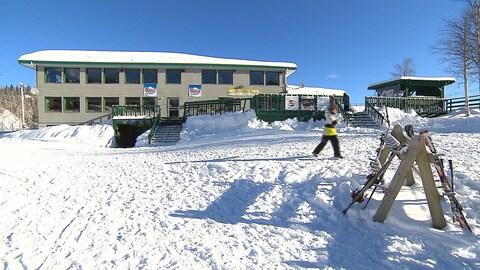 Le chalet avec une personne qui va chercher ses skis en avant-plan