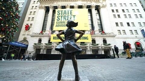 La petite fille est installée en face de l'édifice.