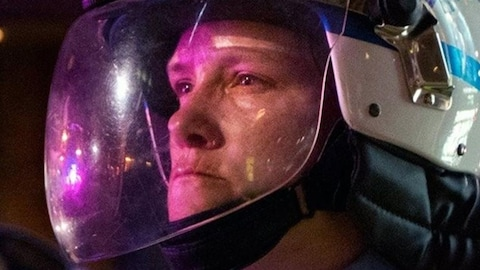 Plan rapproché de la policière avec son casque.