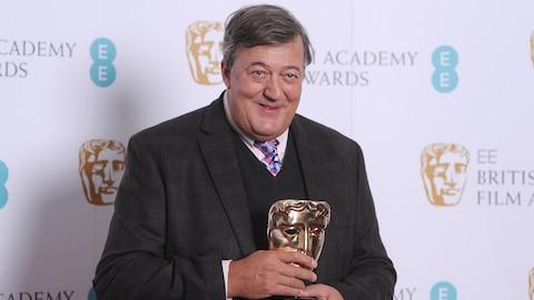 Stephen Fry tient une statuette des BAFTA Awards dans ses mains, souriant aux photographes