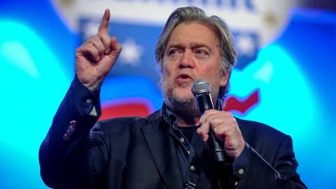 Steve Bannon prend la parole sur une scène, tenant un micro et levant le doigt.