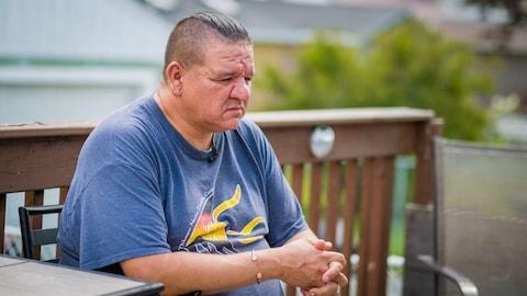 Steve Morrisey assis à l'extérieur sur la terrasse d'une résidence.
